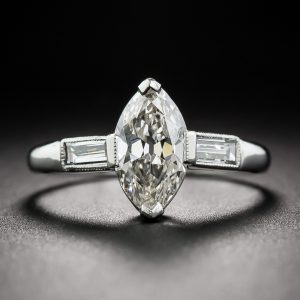 Art Deco Marquise Diamond and Platinum Engagement with Baguette Shoulders and Millegrained Accents.