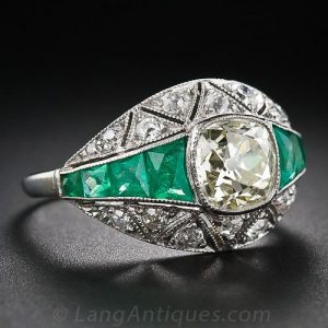 Art Deco Diamond and Platinum Engagement Ring with Calibre Emerald Shoulders an Millegrained Geometric Segments.