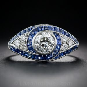 Art Deco Diamond and Platinum Engagement Ring with Swirls of French-Cut Sapphire Outlines and Millegrained Edges.
