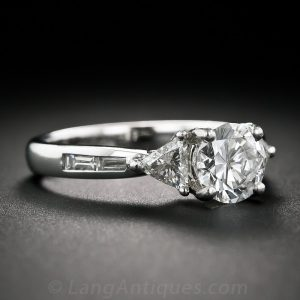 Round Brilliant-Cut Diamond and Platinum Engagement Ring With Trillion and Baguette-Cut Shoulders.
