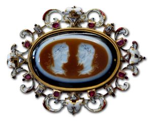 An Antique Cameo, Surrounded by a Symmetrical Array of Diamonds, Rubies and Enameled Gold.