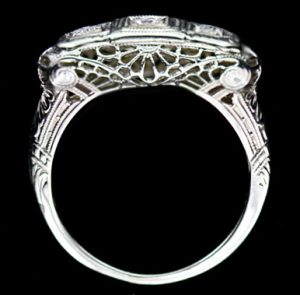 This Late Edwardian, Early Art Deco Three-Stone Diamond Ring in 14 Karat White Gold Features Three Full-Cut Diamonds, Weighing .22 Carat Total, Set Horizontally in Square Panels. Scroll and Lace Motif Filigree Work Accent the Ring's Gallery.
