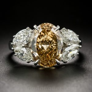 Oval Fancy Deep Brownish Yellowish Orange. Diamond with Two Pair of Marquise-Cut Side Stones.