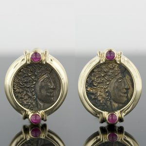 Brightly Polished 14 Karat Yellow Gold Neo-Classic Style Bezel Earrings, Highlighted with Ruby Cabochons are the Frames for the Pair of Replica Ancient Coins Encased. The Coins, Having an Oxidized Finish, Depict the Profile of a Greco-Roman Emperor.
