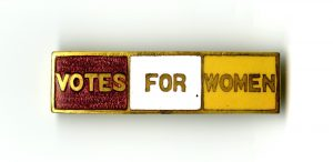 "Enameled Pin with the Slogan ""Votes for Women"" in the Purple, White, and Yellow of the National Woman's Party."